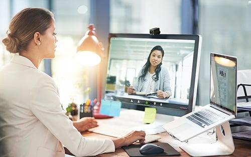 女士坐在桌前使用電腦進行Zoom視像會議