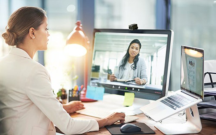 A woman at a desk having a Zoom video meeting on her computer.