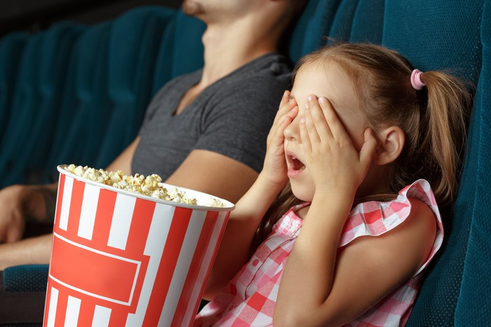 A young girl covers her eyes and has a big bucket of popcorn on her lap in a theater.