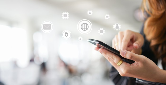 Woman using mobile device with symbols overlaid for email, global internet, and other applications.