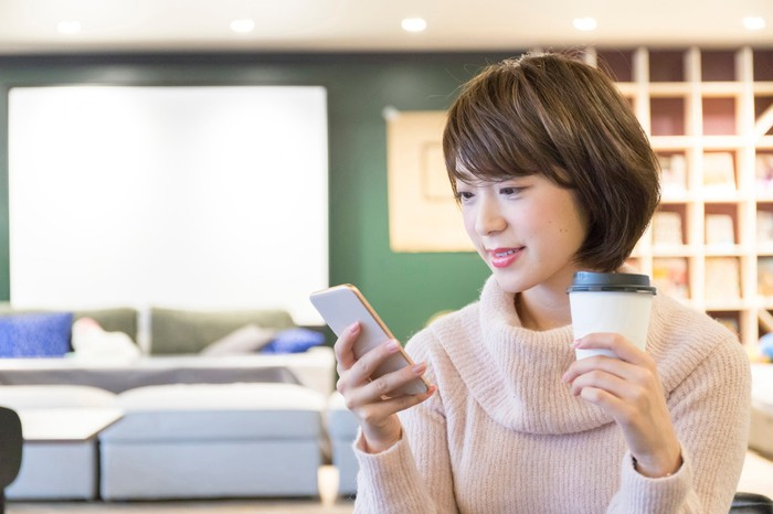 A woman looks at a mobile phone while holding a cup of coffee.