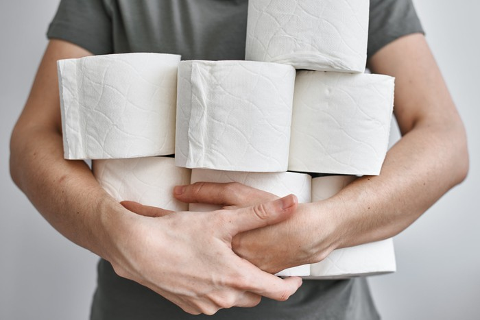 Man holding several rolls of toilet paper.