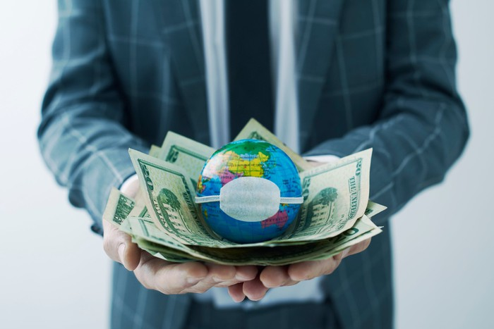 A businessman holds a pile of dollars and a globe wearing a mask.