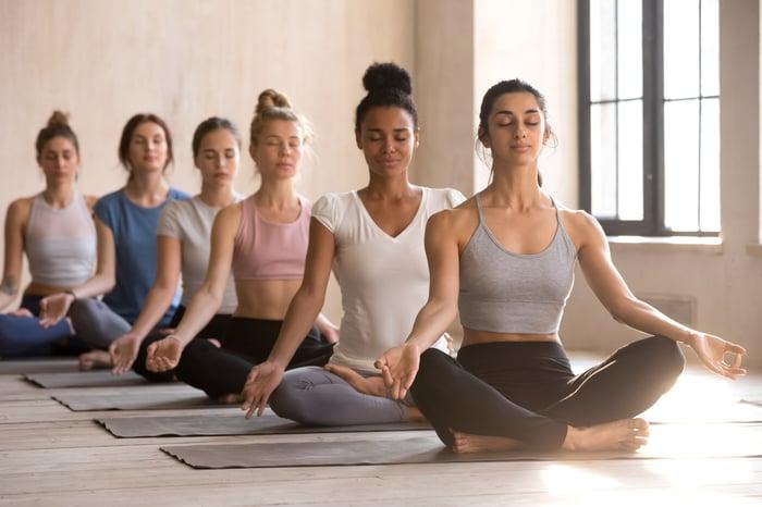 A group of women attend a yoga class.