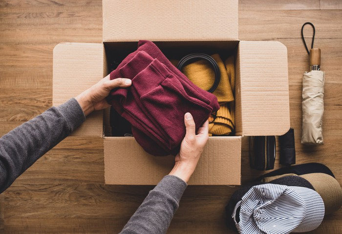 A woman removes clothes from a box.