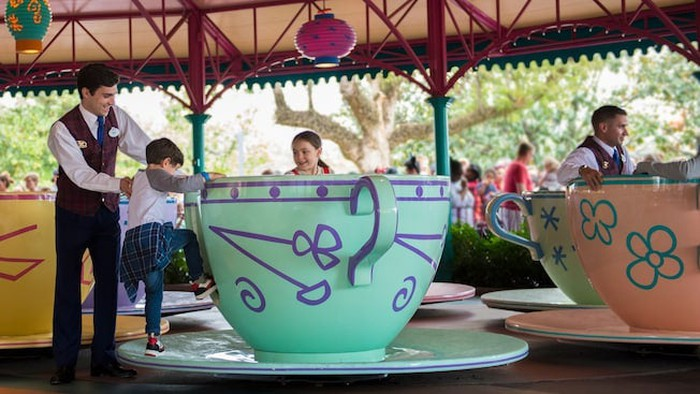 A child is helped into a ride vehicle at Magic Kingdom.