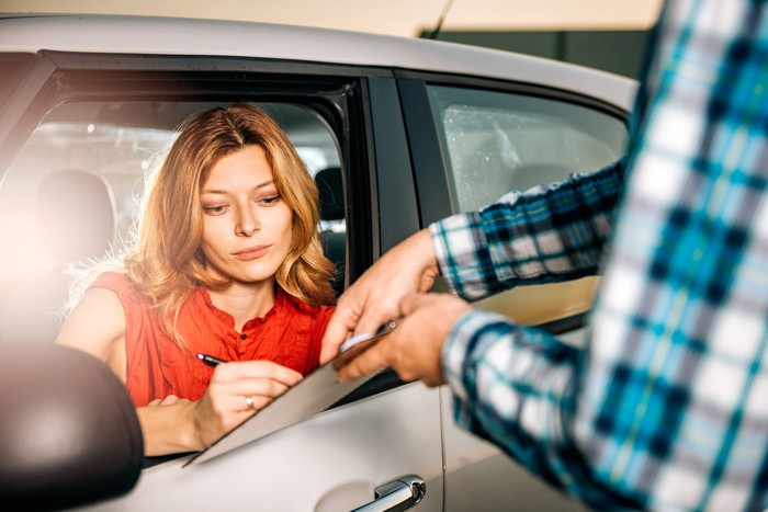 woman signing for vehicle rental