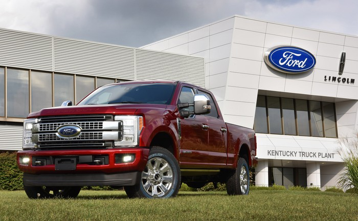 A red Ford Super Duty pickup parked in front of the factory that built it, Ford's Kentucky Truck Plant in Louisville.