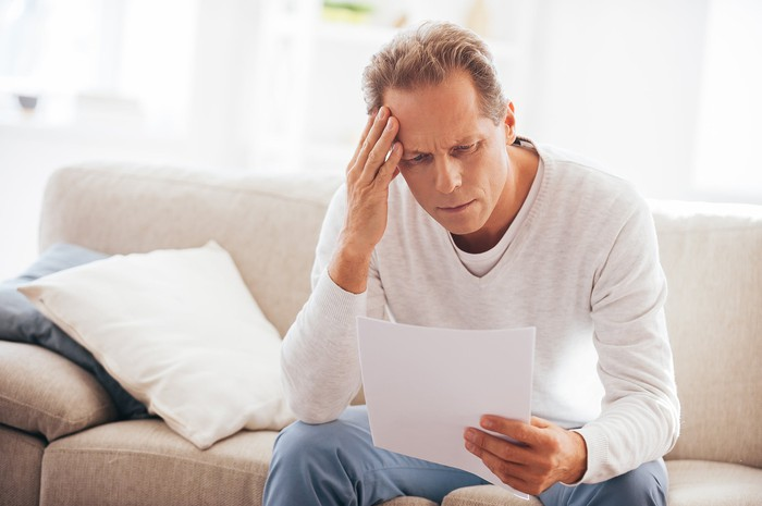 Man sitting on couch looking at document with pained expression