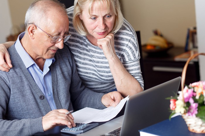 Older man and woman at laptop; man holds document and types on calculator
