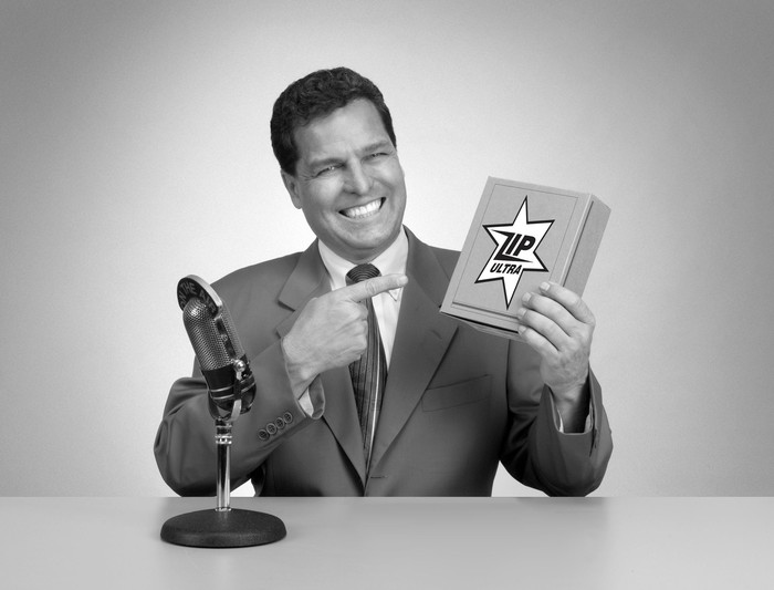 1960s TV announcer pointing to a sponsored product, in black and white