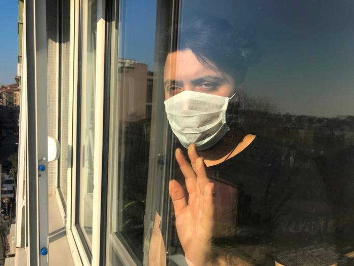 Sad woman in a face mask places hand on the window and looks outside