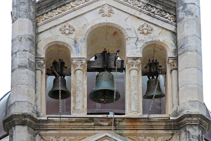 Three large church bells ringing in a tower