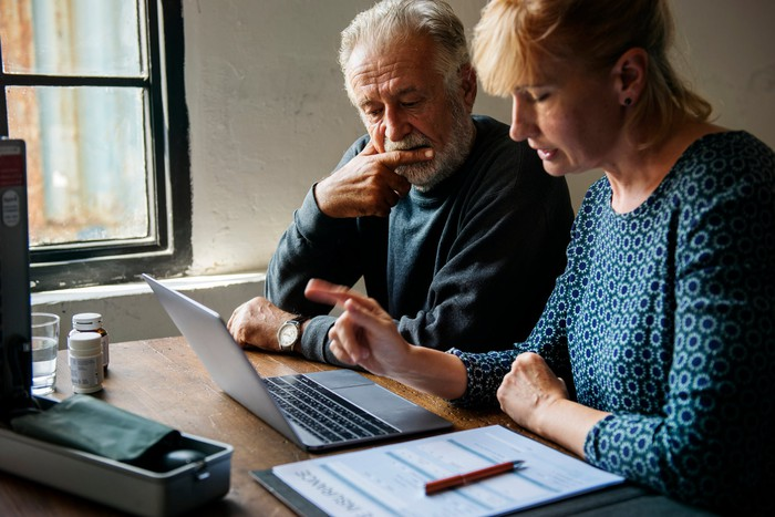 An elderly couple at a laptop looking concerned.