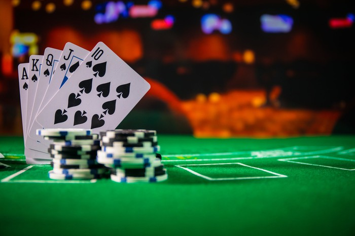 Stacks of chips and a hand of cards sit on a gambling table.