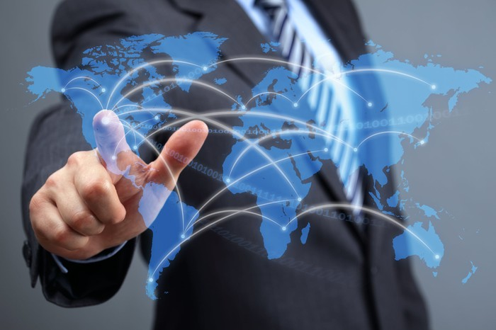 A person in a business suit is pointing to a digital map of the world.
