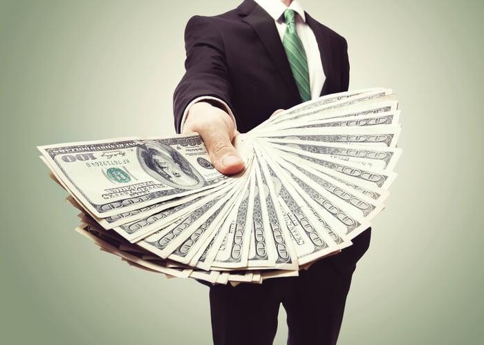 西裝男手中扇開的美金的特寫。