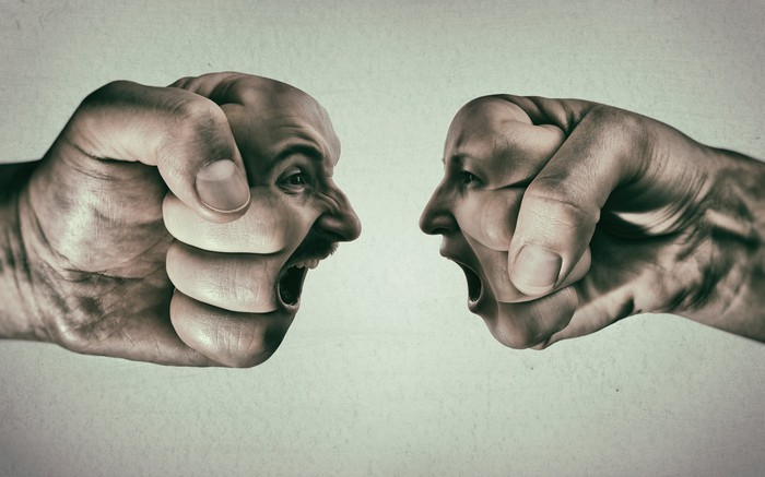 A shouting duel between two faces superimposed on fists.