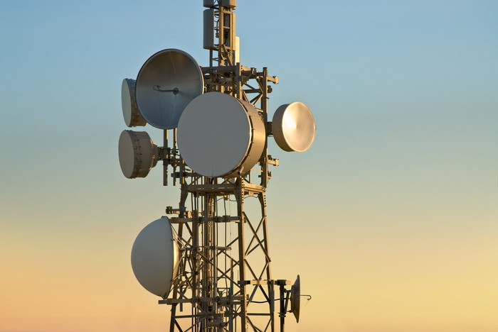 A cellular tower with numerous dishes attached.