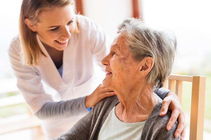 A young woman in a medical coat smiling, standing, and placing her hands on the shoulders of a seated elderly woman.