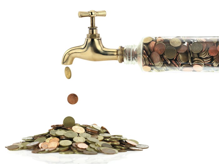 A water faucet dispenses coins onto a pile of coins on a plate.