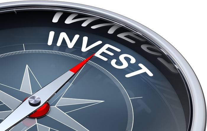 A compass needle is pointing towards the word invest.