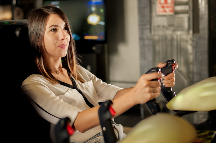 A woman plays an arcade game.