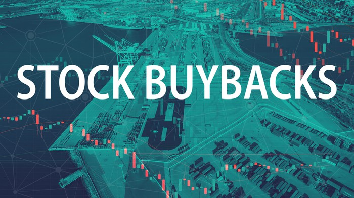 The words Stock Buybacks in front of a stock screen with money.