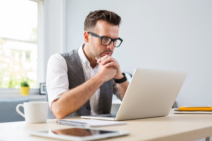 Man with look of concentration at laptop