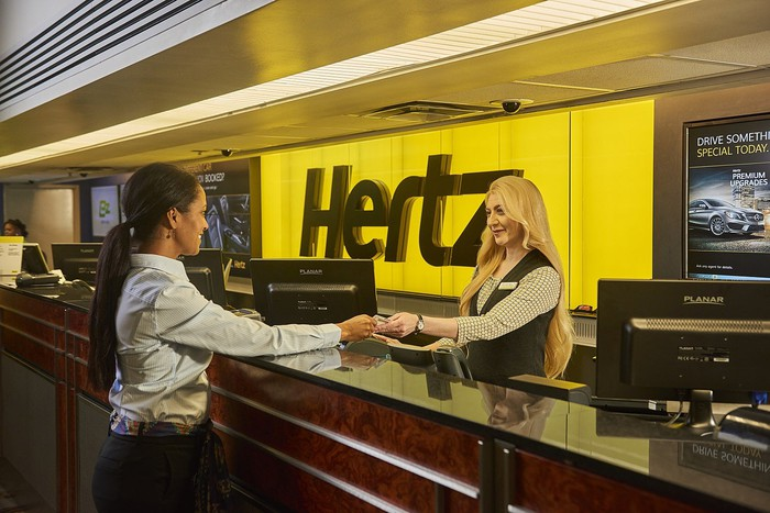 Clerk handing keys to customer at a Hertz counter, with sign and logo behind them.
