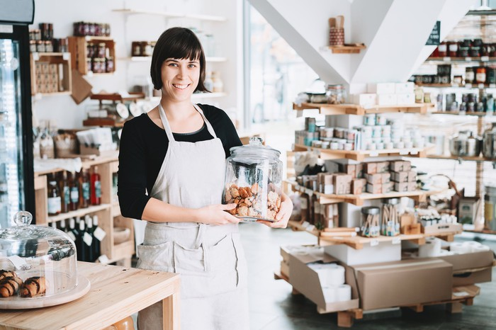 Smiling apron-clad woman in store holding cookie jar