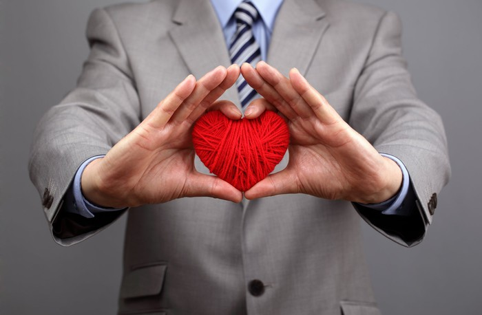 A person in a business suit holding out yarn in the shape of a heart.