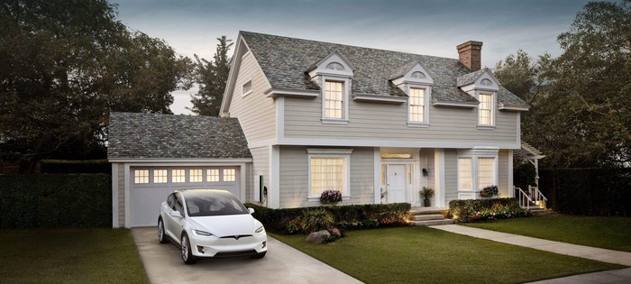 House with a Tesla car in the driveway and a Solar Roof.