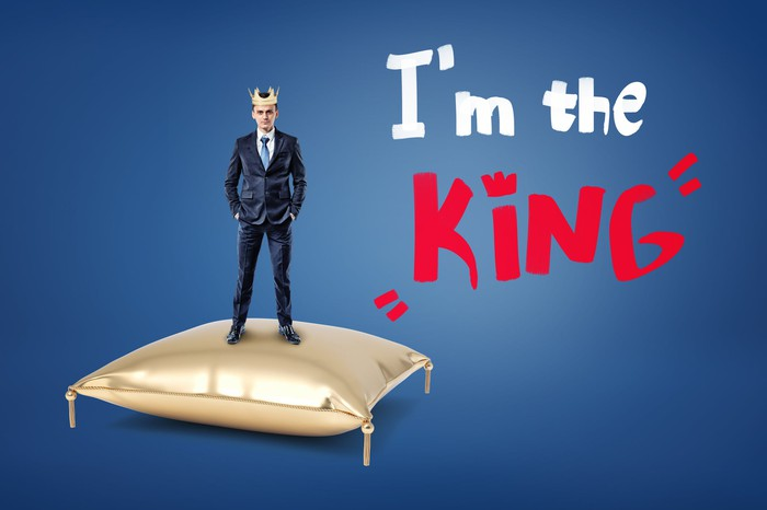 """Businessman wearing a crown while standing on a pillow saying """"I'm the king."""""""