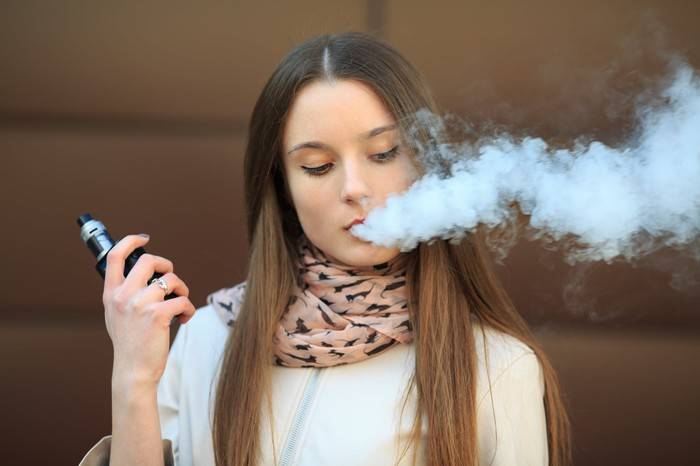 A girl holding a vape pen and exhaling a cloud of smoke