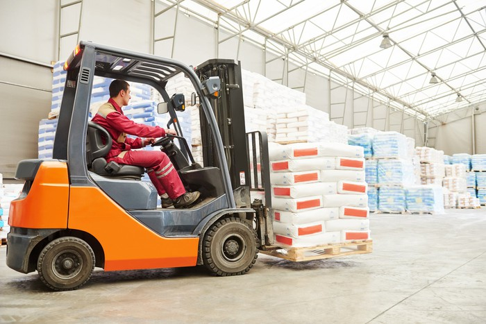 A forklift moves a loaded pallet in a warehouse.
