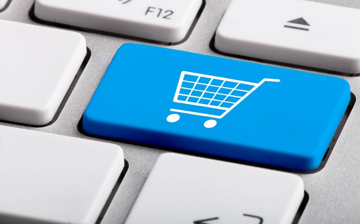 A computer keyboard featuring blue key with a shopping cart to illustrate e-commerce.