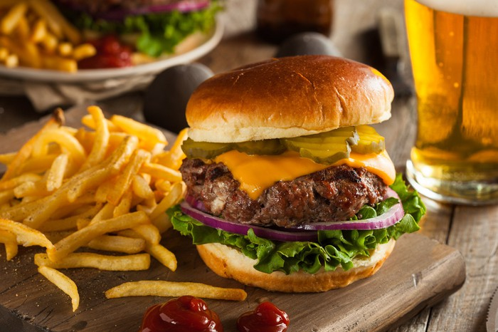 Beef burger beside fries on a wooden platter