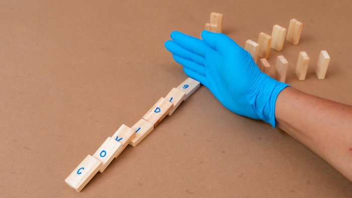 Gloved hand separating fallen wooden dominoes spelling out COVID19 from a set of standing dominoes