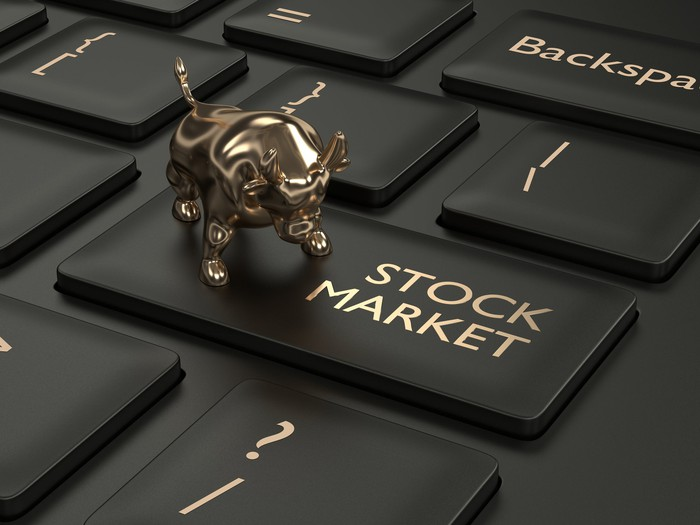Tiny gold bull on top of stock market key on a PC keyboard.