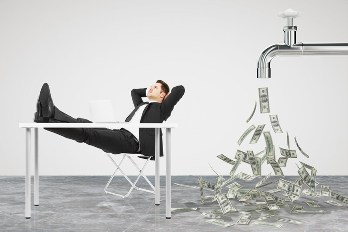 Businessman sitting with his feet propped up on table and money flowing out of a giant faucet behind him