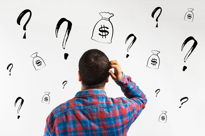 Man with hand next to head looking at white wall with question marks and money bags drawn on it