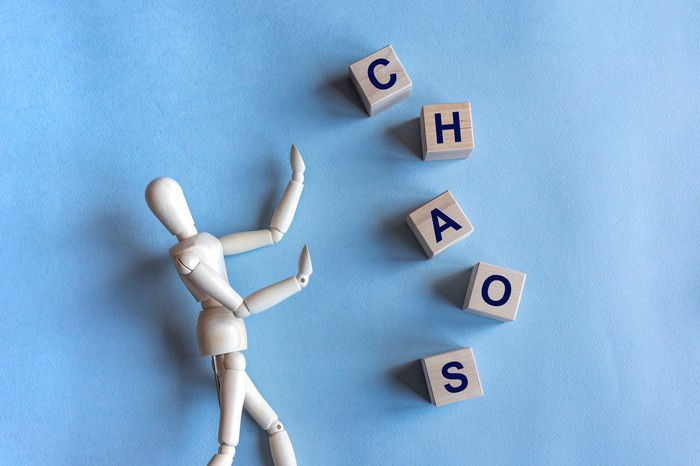 Chaos written in wooden cubes and a wooden mannequin on blue background.