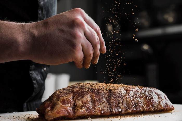 A hand sprinkles seasoning on a piece of meat