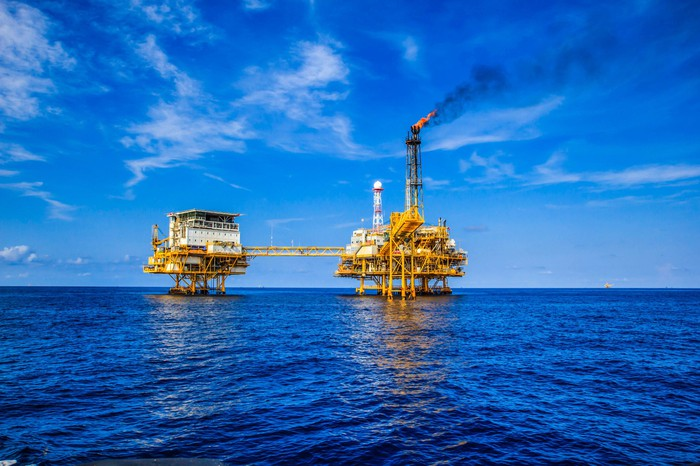 deep sea oil rig against blue sky with gas flaring