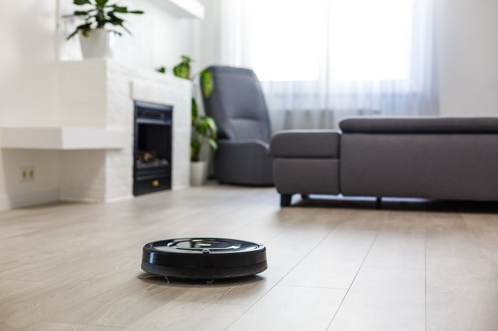 A robotic vacuum in a living room with a fireplace, a couch, and a matching chair