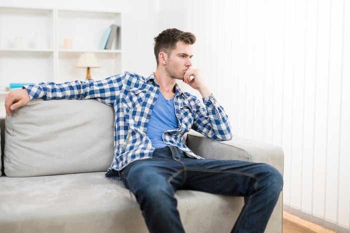 Man sitting on couch, deep in thought