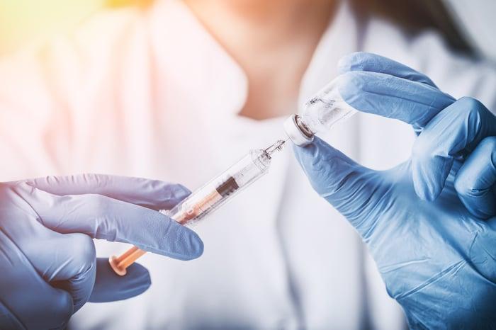 Gloved hands holding syringe and vaccine bottle