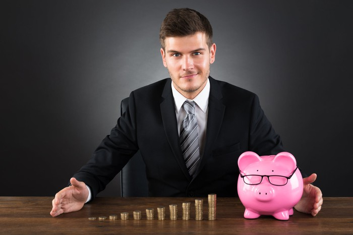 Smiling man in a suit sitting behind a piggy bank and increasing taller stacks of coins.