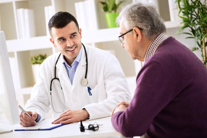 Older man talking to doctor.